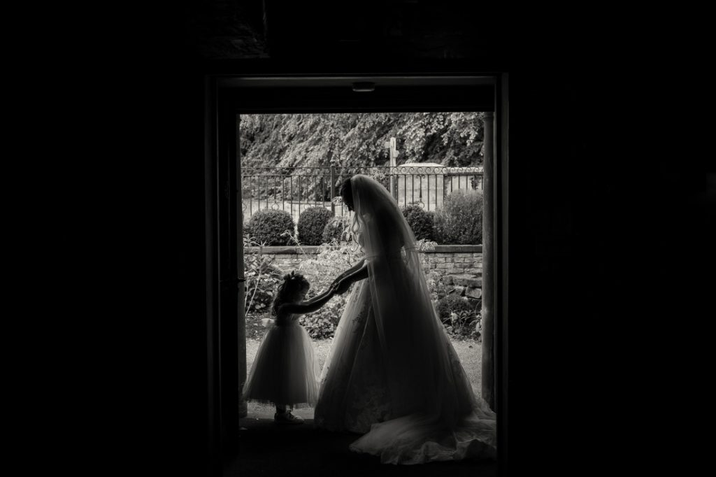 bride and flowergirl silhouetted in the doorway