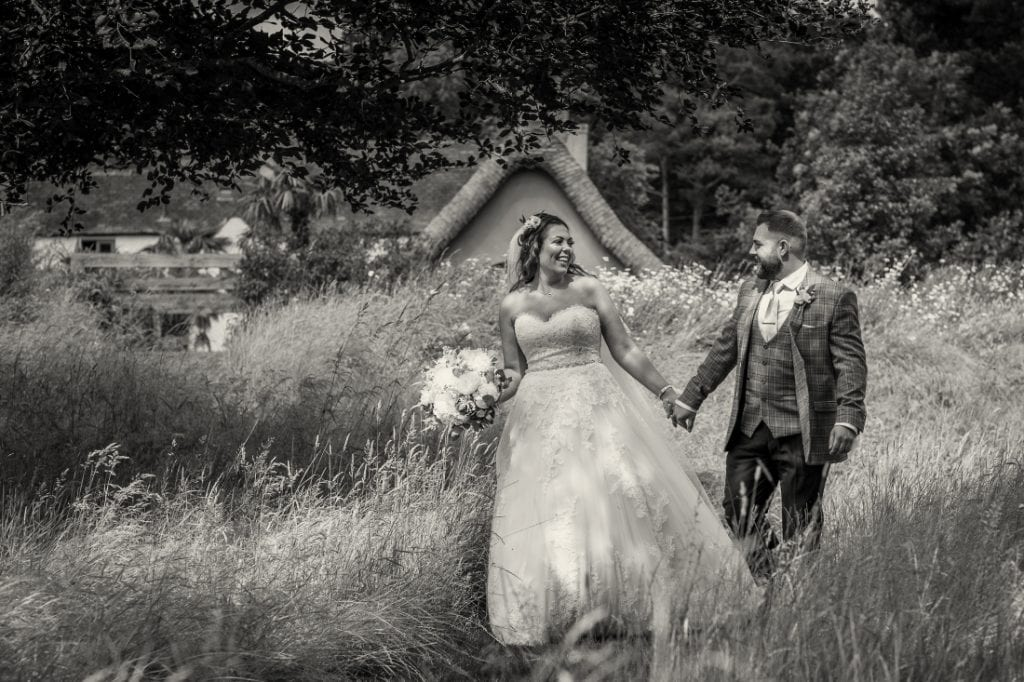 bride and groom hand in hand laughing as they walk through the meadow