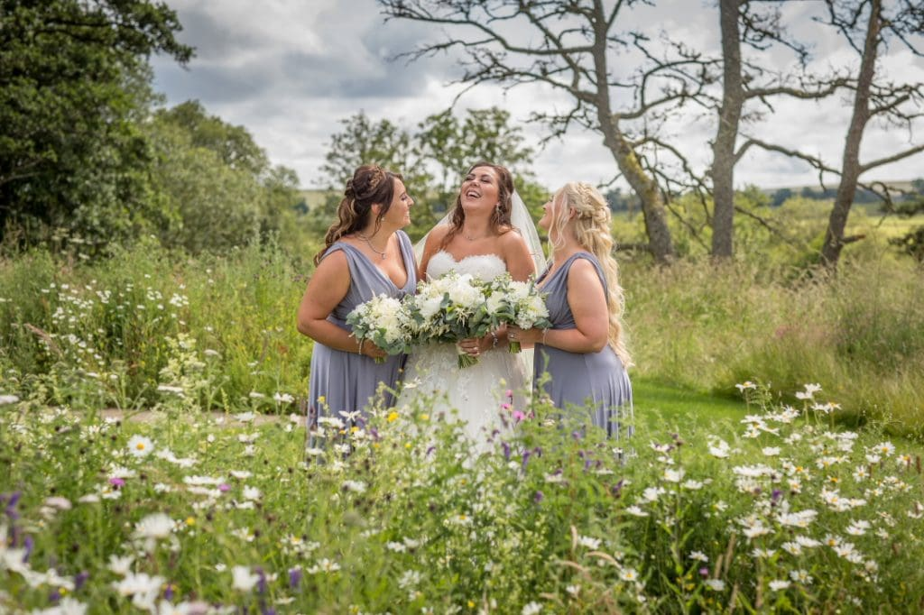 bride and bridesmaids laughing in the meadow