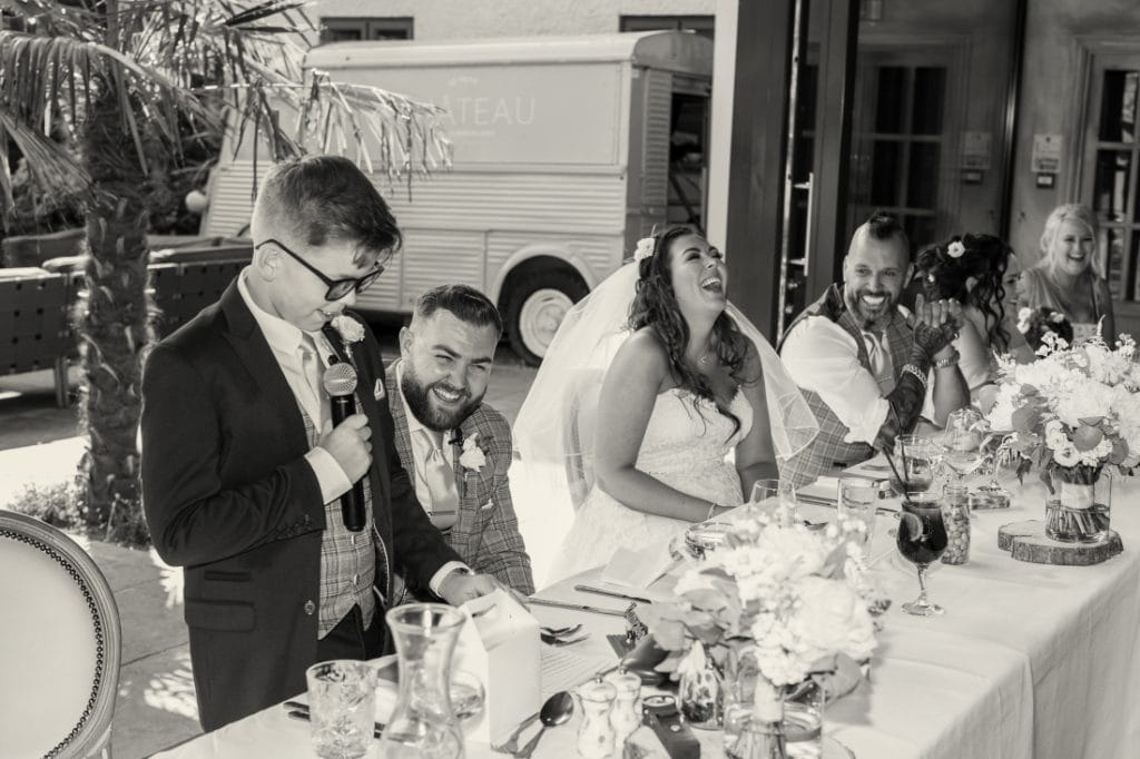 bestman and bride and grooms son making his speech with top table laughing