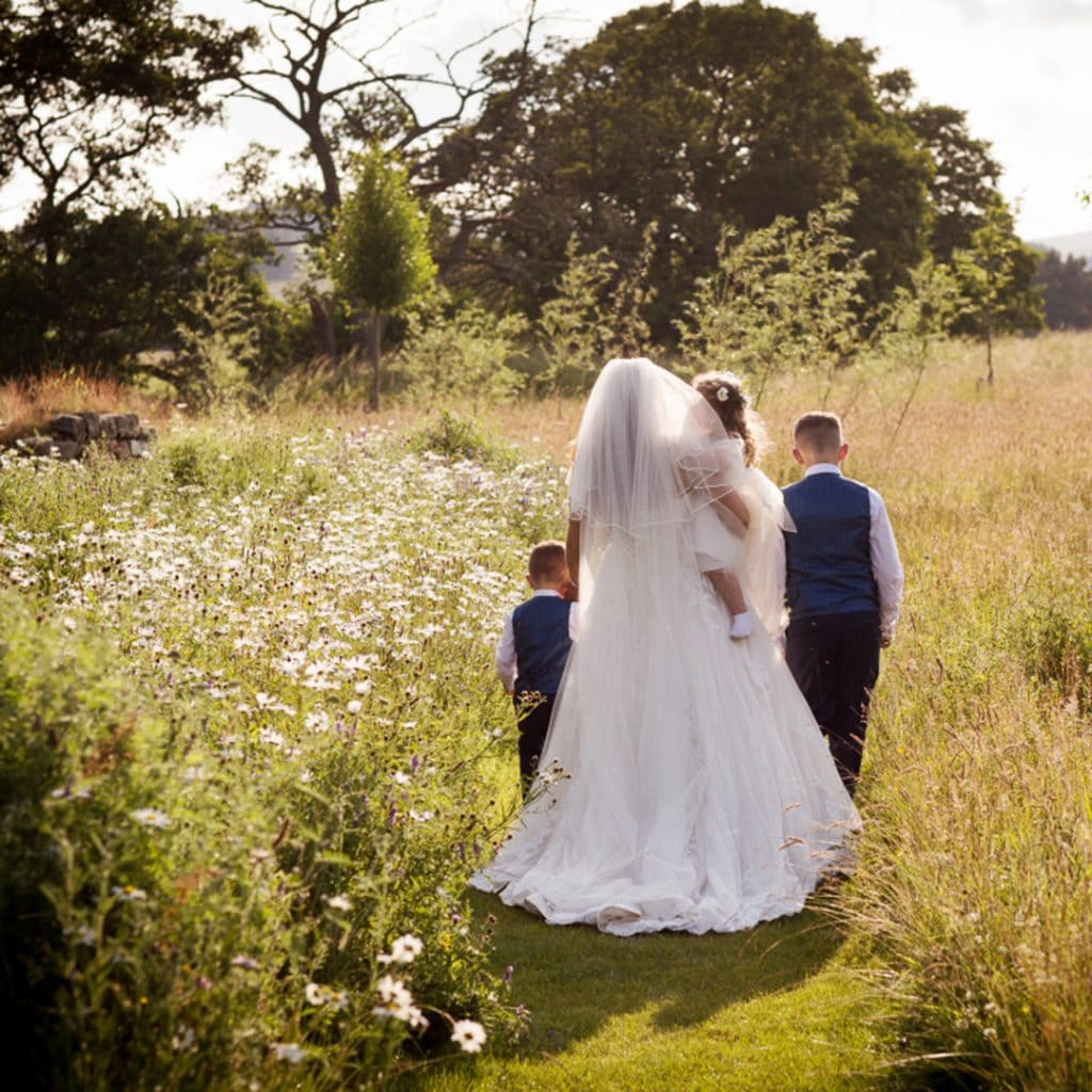 bride walking in the meadow with her children