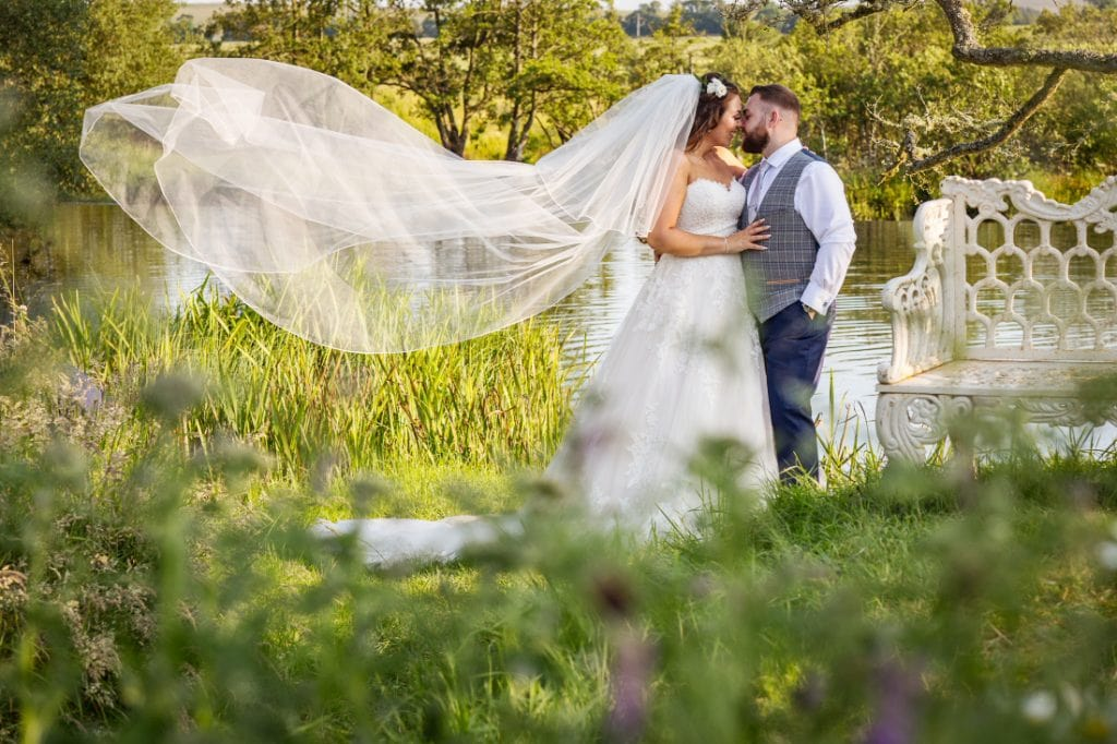 bride and groom by waters edge with viel blowing in breeze