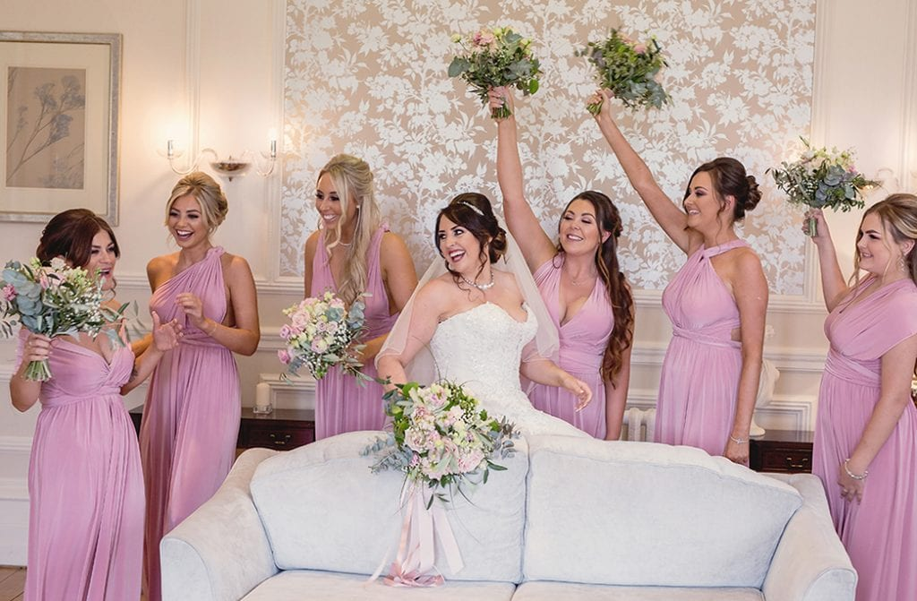 bride and bridesmaids throwing their flowers in the air
