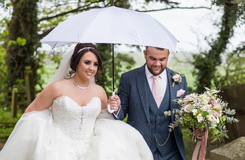 bride and groom walking from church under and umbrella