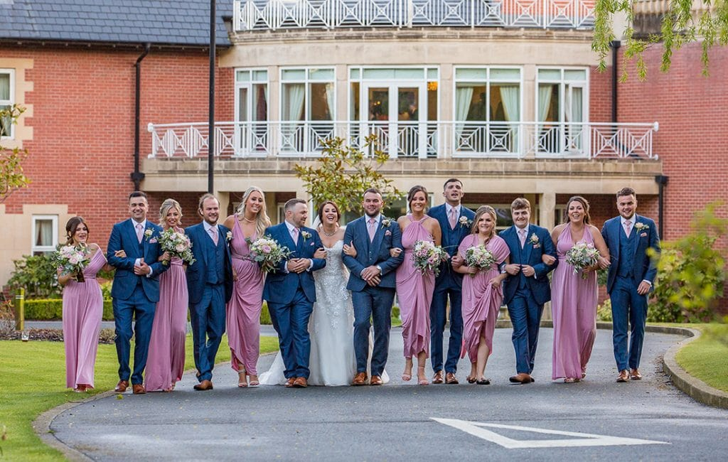 bridal party walking and laughing outside Rockliffe Hall