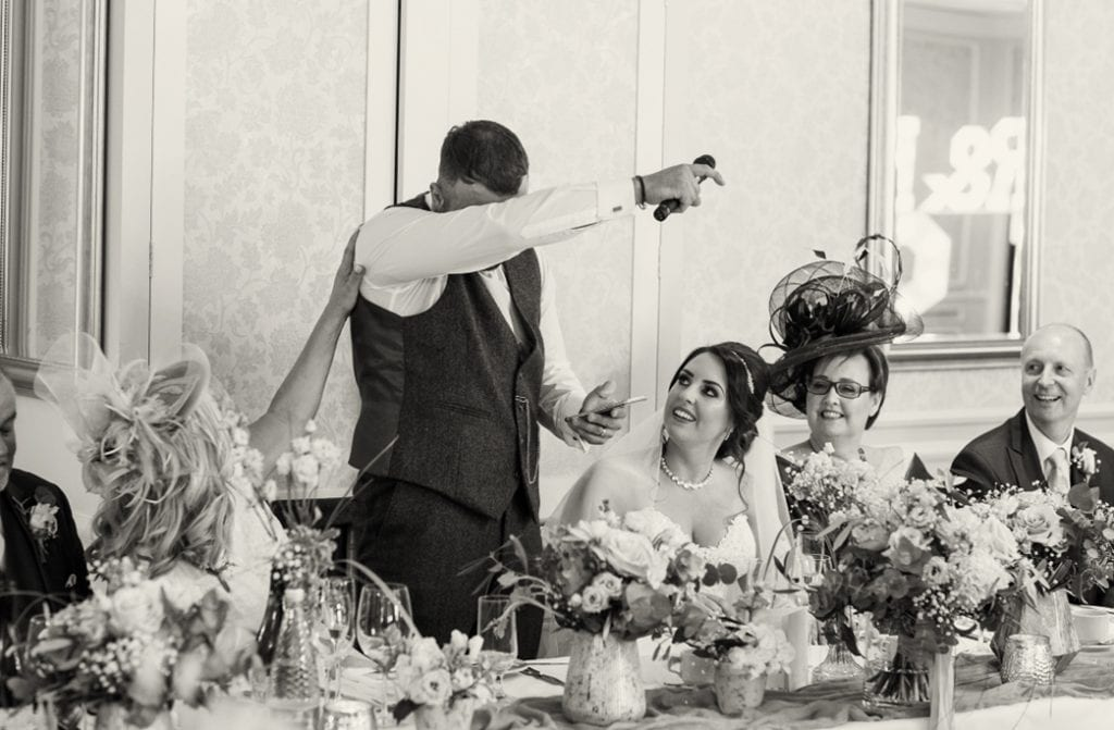 groom wiping a tear from his face as the parents look on