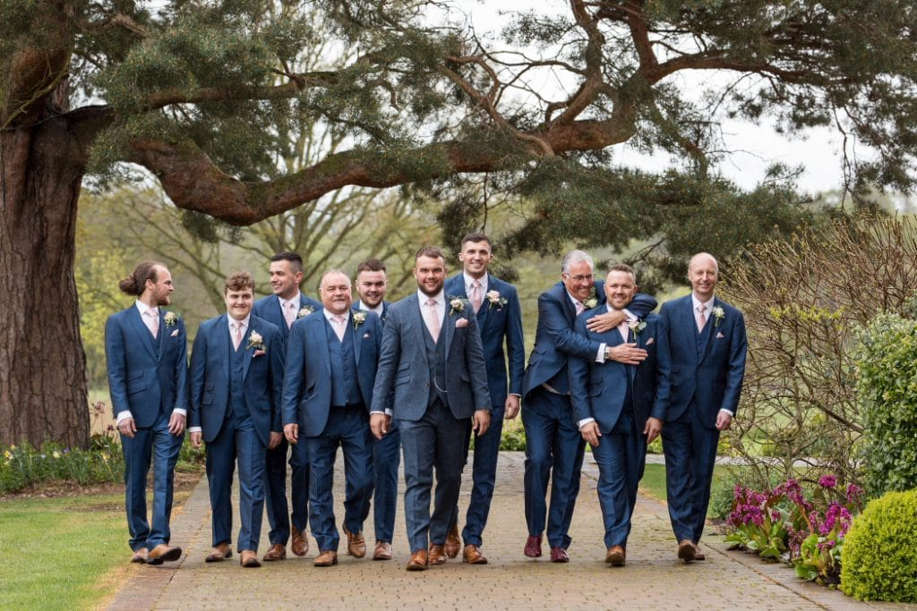 male wedding party walking and hugging