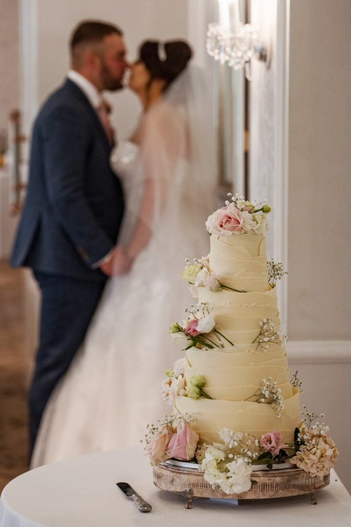 bride and groom kissing stood by their wedding cake