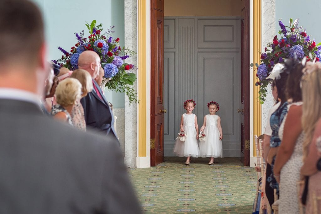 2 flowergirls walking into the ceremony room with the groom out of focus in the foreground creating a childhood memory