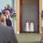 2 flowergirls walking into the ceremony room with the groom out of focus in the foreground.