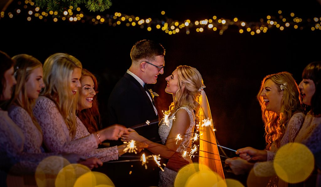 Anyone can take a photo, bride and groom image taken at Headlam Hall.  The couple are holding onto each other outdoors at night and their bridesmaids are swirling sparklers in front of them.