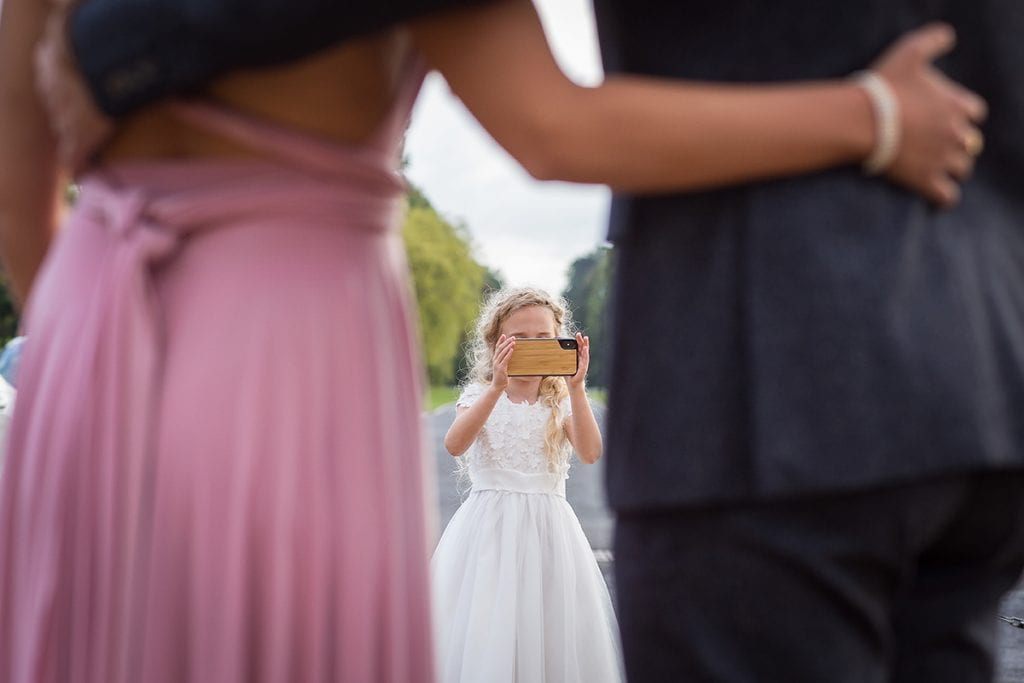 Anyone can take a photo, a flower girl at an Acklam Hall wedding taking a picture of a bridesmaid and her partner with an iphone.