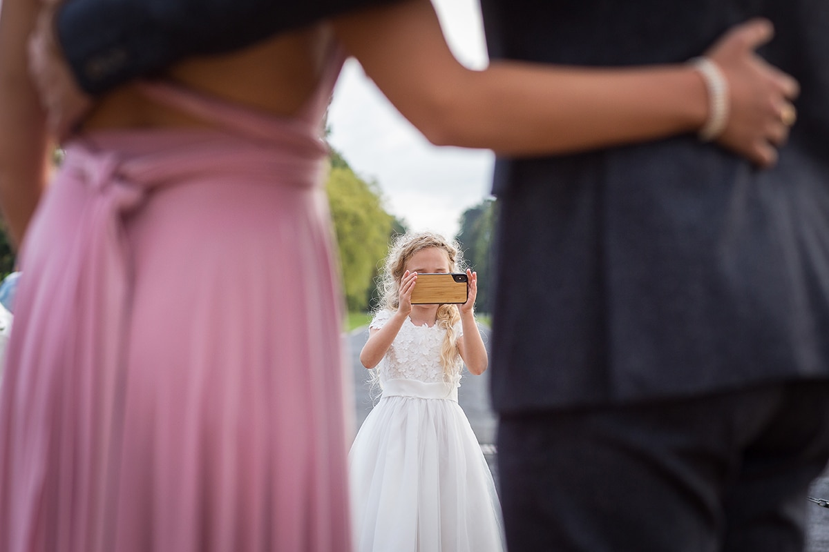 flower girl taking a photo with an iphone of a bridesmaid and her partner.