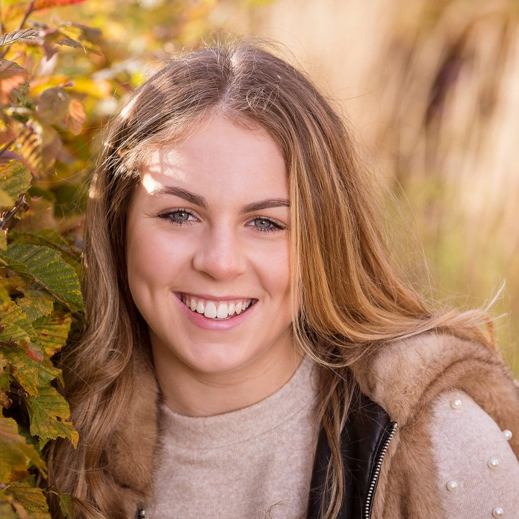 Christmas present portrait, young girl photographed smiling in the garden at Wynyard Hall Gardens, beautiful dappled light.  Location Portrait Photography