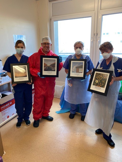 4 hospital staff wearing PPE holding framed photographs