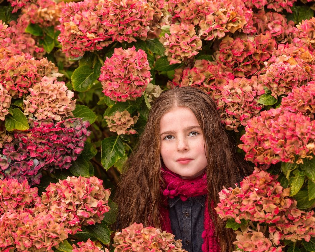 young girl surrounded by hydrangeas