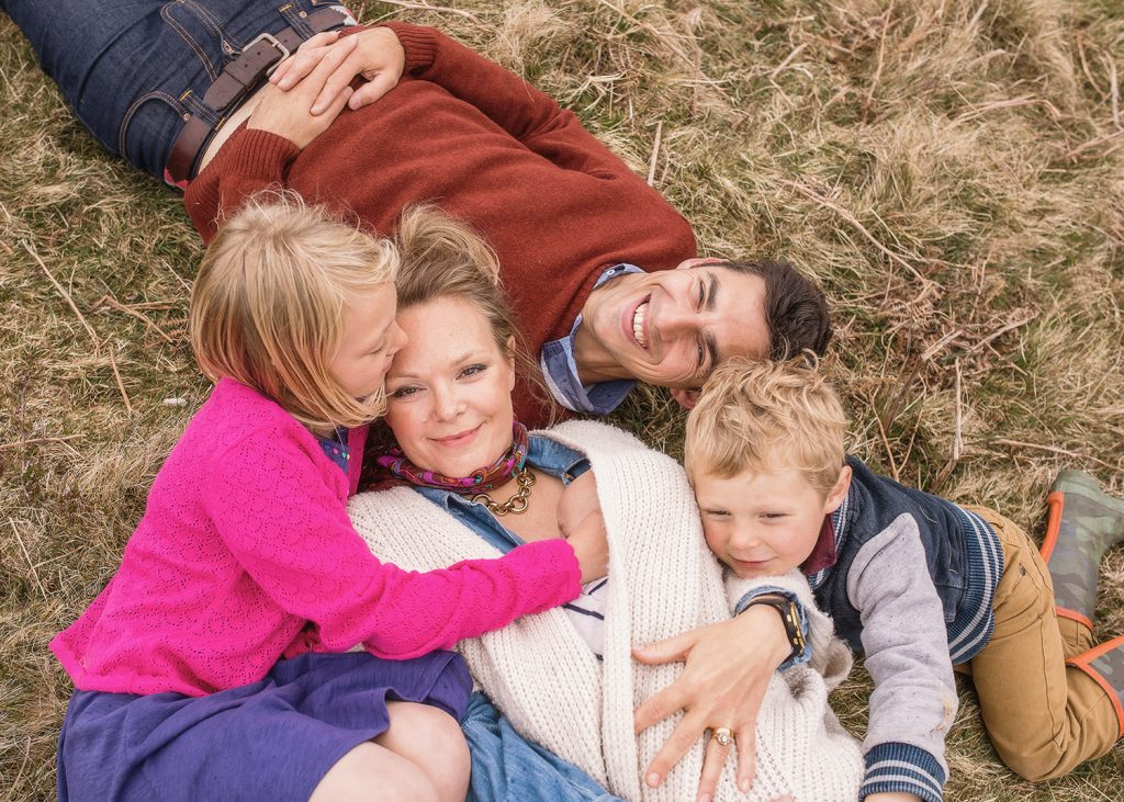 a family of 5 laid on the grass and photographed from above
