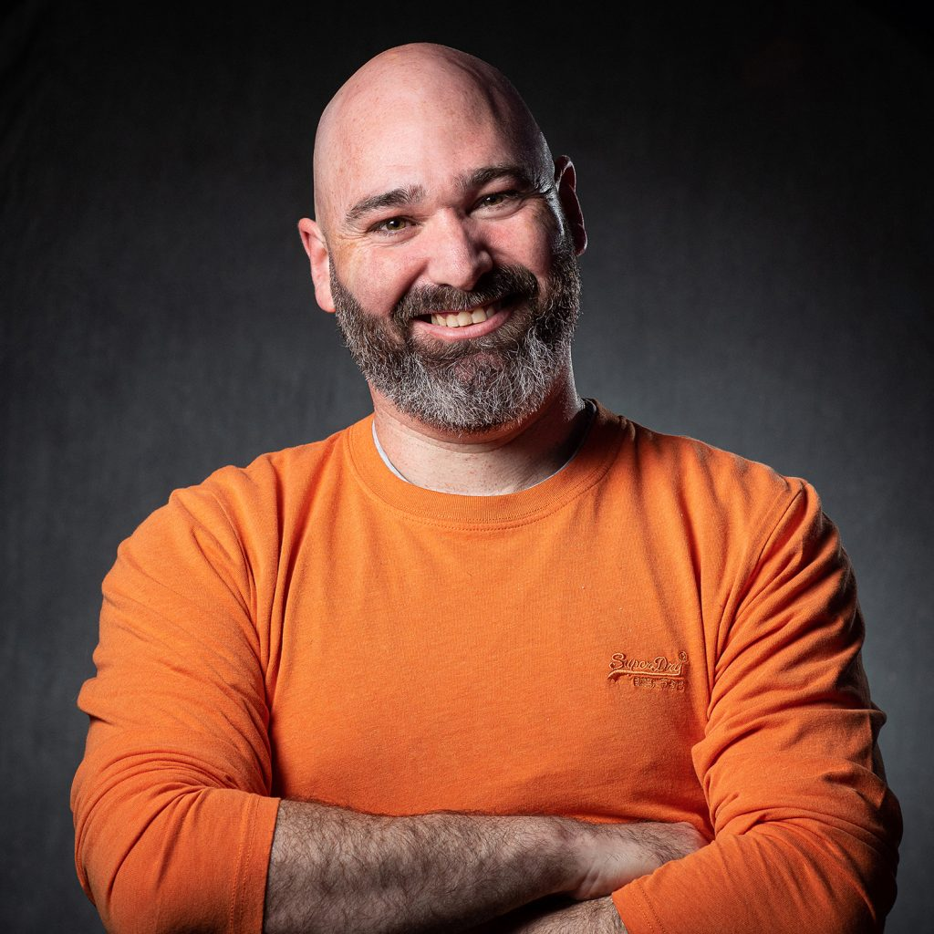 bar owner in a bar owners pose, studio style portrait
