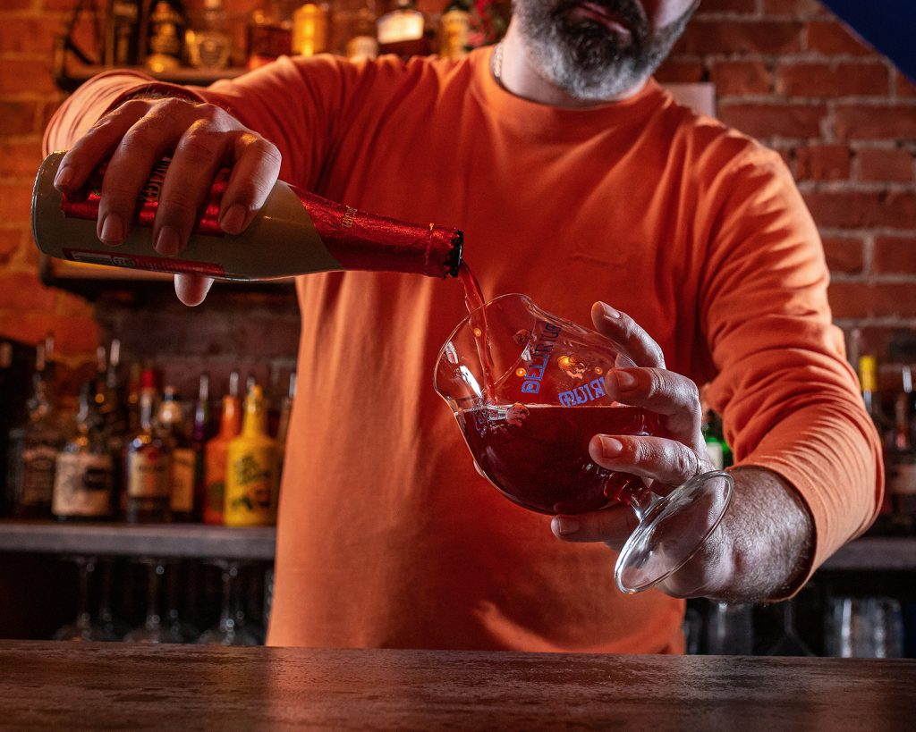 bar owner pouring a craft ale into a fancy glass
