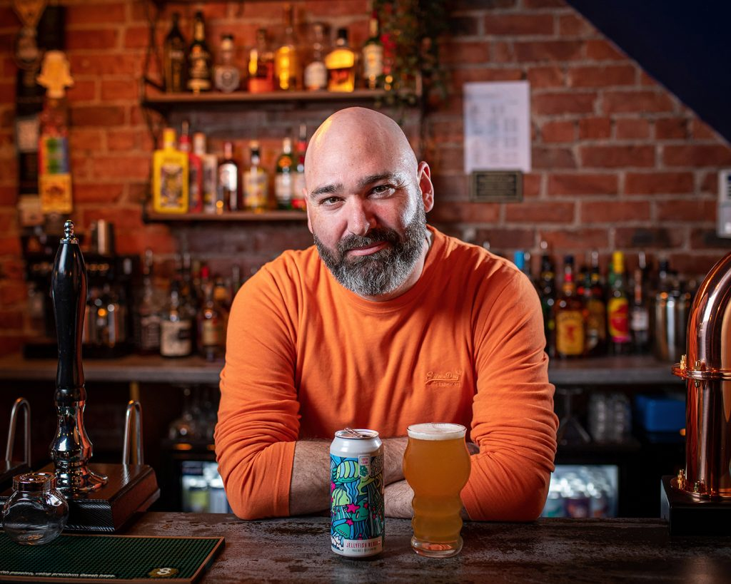 portrait of bar owner at his bar with his fave tiple