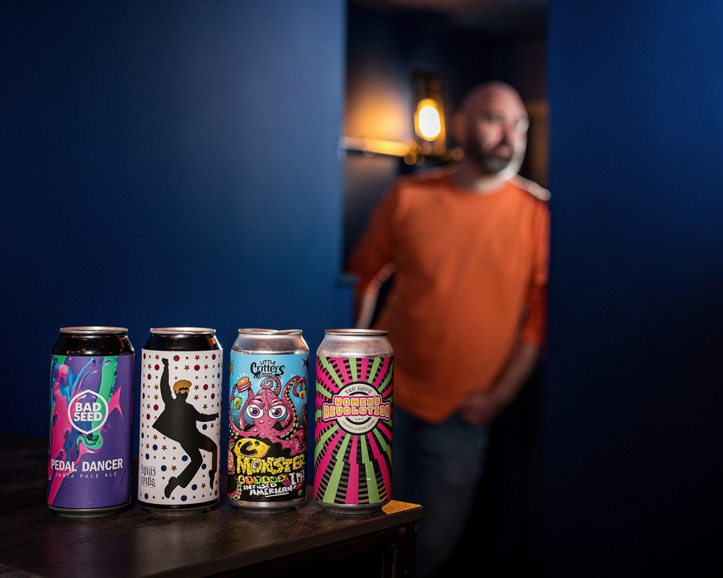 bar owner stood in doorway with cans of beer in the foreground